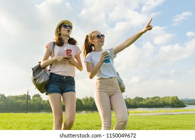 Girl friends are walking in the park in nature. Girls walk along the green lawn, talk, have fun