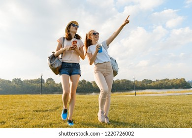 Girl friends are walking in the park in nature. Girls walk along the green lawn, talk, have fun.