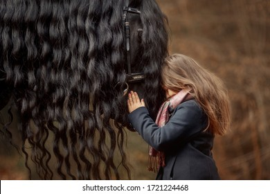 Girl with friesian horse autumn forest