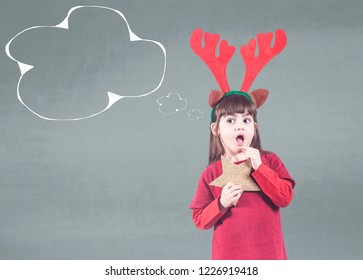 Girl full of Christmas spirit with elf hat holding a golden star thinking about her wishes