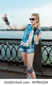 Girl with full protection wear standing and taking selfie on phone and holding peace sign. Young fit women girl in sunglasses, jeans shorts and a jacket on roller skates on river embankment