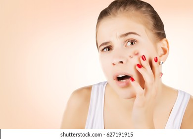 girl with funny disgusted face examines her pimples