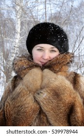 The girl in fur coat poses in the forest background