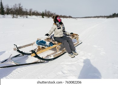 a girl in a fur hat and warm clothes travels north, skates on big sledges