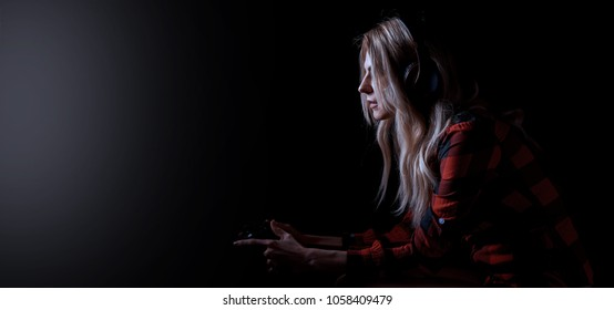 girl gamer in headphones and with a joystick in her hands playing network games preparing to participate in international competitions in e-sports