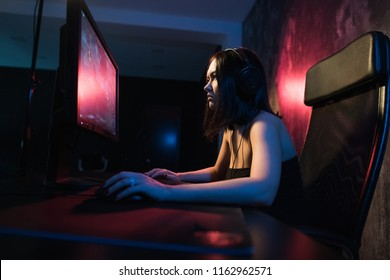 girl gamer in headphones and with a keyboard and mouse in her hands playing network games preparing to participate in international competitions in e-sports