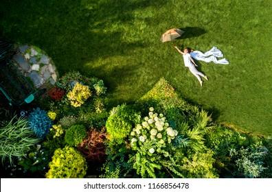 girl in the garden with an umbrella, top view
