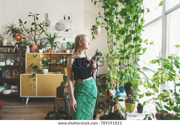 girl gardener with a cat in her arms looking out the window against a background of indoor plants