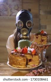 Mädchen in einer Gasmaske am festlichen Tisch mit einem Kuchen