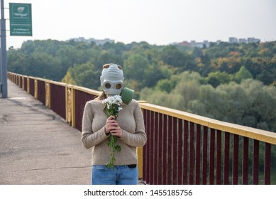 A girl in a gas mask sniffs flowers. Dirty air in the city. June 15, 2017, Belarus, Grodno