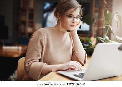 Girl gazing at profile page of handsome man, browsing through dating sire while sitting in cafe with laptop, leaning on hand and gazing at notebook screen, sitting in cafeteria near window