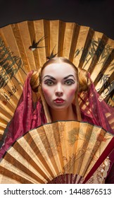 girl in geisha costume with fan on black background