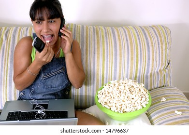 Girl of generation Y doing many things at the same time (calling,  watching tv, Surfing the web and eating popcorn)