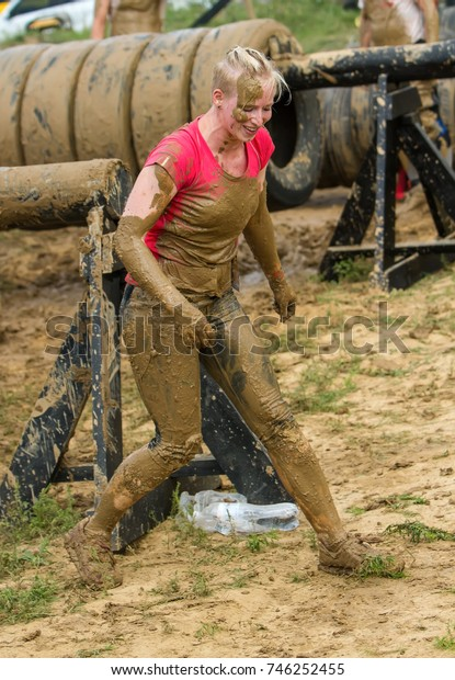 The girl gets up after the emotional overcoming of the obstacle made of tires.