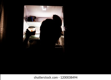 Girl gets food at night from the fridge
