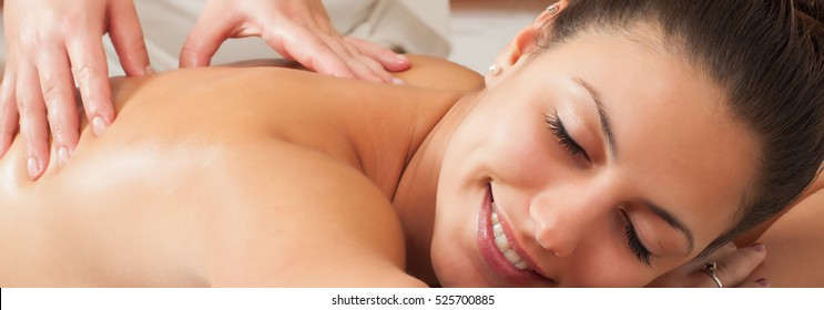 Girl getting back massage in massage salon, health spa.
