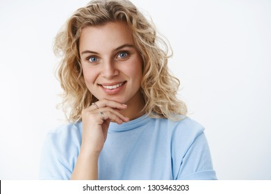 Girl getting interested and curious as listening intriguing speech wanna try concept holding hand on chin thoughtful and smiling delighted as liking plan gazing happily and pleased at camera
