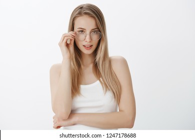 Girl getting interested as listening intriguing idea, taking off glasses, touching frame, posing with slightly opened mouth and sensual expression wearing white top over gray background