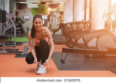 Girl getting ready for training in gym. Girl in gym smiling, looking at camera. Lens flare