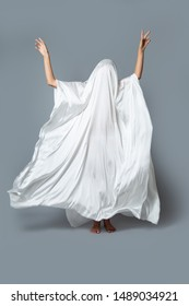 A girl in a Ghost costume on a gray background in the Studio. Halloween minimal concept.