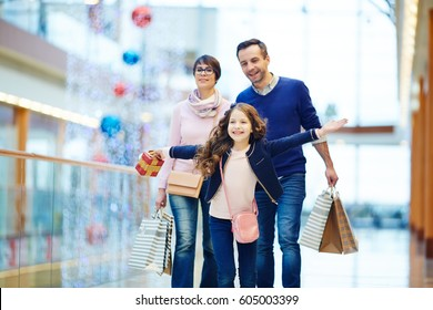 Girl with gift box running in front of her parents during shopping