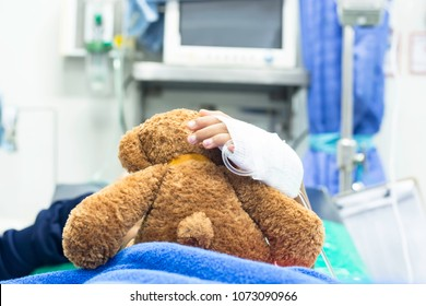 The girl was given intravenous fluid hugging a teddy bear while lying in the emergency room of the hospital.