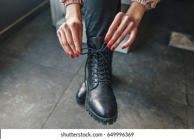 The girl gives up laces on black leather boots red nails. She sits in cafe. As probably, on the street winter.