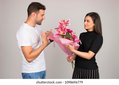 Girl giving flowers to her boyfriend, couple celebrating special occasion concept