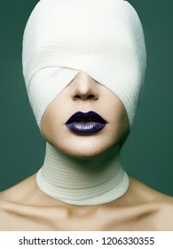 girl in glamorous mask for halloween. female face wrapped in bandage. beauty make-up woman, blue lipstick. plastic surgery