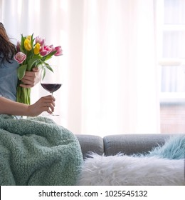 A girl with a glass of wine and a bouquet of yellow and pink tulips on a sofa in the living room. The woman by the window. Good morning. A gift for a beloved woman. Cover. Cozy house