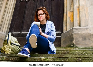 Girl in glasses with backpack sitting on the stairs and writing something in her notebook. Erasmus student, studying abroad and tourist concept