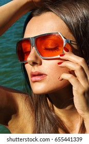 Girl in glasses with colored glasses posing against the sea close-up portrait