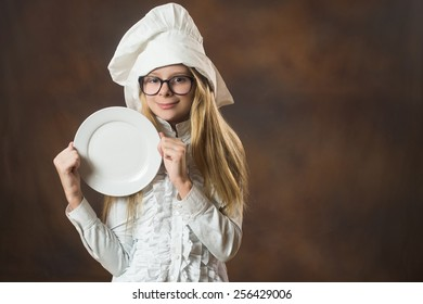 Girl with glasses and dressed in chiefs hat holding white plate