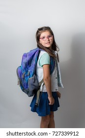 A girl with glasses is excited and nervous for her first day of school.