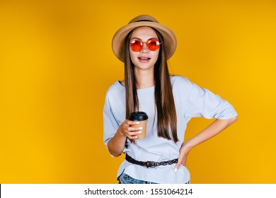 girl in glasses and a hat in a yellow studio stands and holds a glass of coffee in her hand