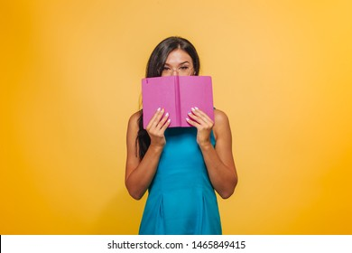 A girl with glasses on a yellow background in a blue dress Covered her face with a pink notebook