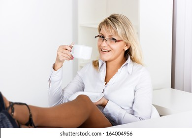 A girl with glasses resting with a cup of coffee in the office
