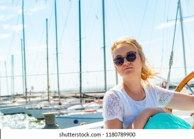 A girl in glasses sits near the wheel next to on the deck of a yacht looking around