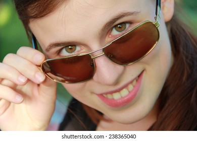 girl with glasses smiling .