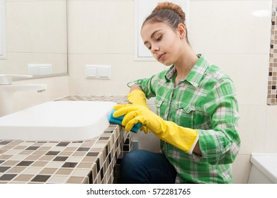 Girl in gloves cleans the sink in the bathroom with a sponge and detergent
