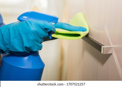 A girl in gloves disinfects the surface with a sanitizer antiseptic. Treats the door handle with an antibacterial agent. room antiseptic disinfection. Coronavirus prevention covid-19 2019-ncov