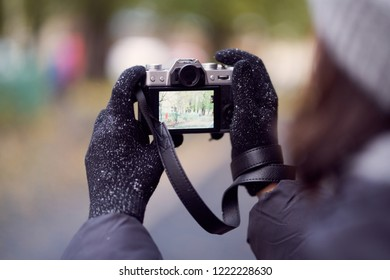 girl in gloves and mirrorless camera. view from over the shoulder, the camera in hand.