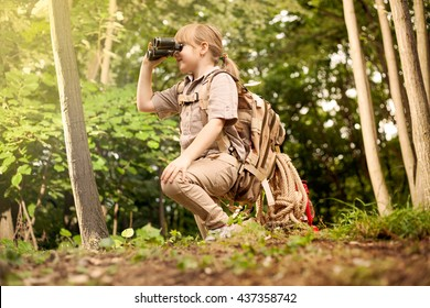 girl go hiking with backpacks on a forest road bright sunny day