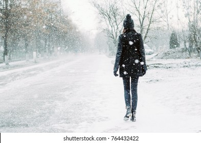 The girl goes by the road that is covered with snow. Many snowflakes are flying in the air, a blizzard is coming.