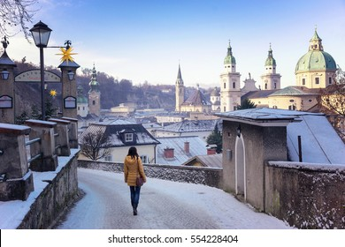 Girl goes on a snow-covered winter beautiful city.Walking through the streets of snow-covered city Medieval. Very nice view of Salzburg.Winter town.Journey in winter Austria. Euro-trip.