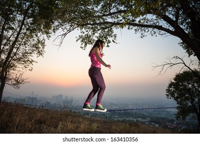 The girl goes and shows tricks on tightrope at sunset and the city slack-line