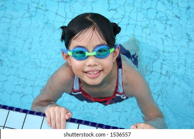 Girl with goggles in the swimming pool