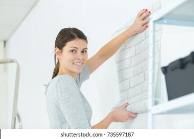 girl going to cover the wall with wall paper
