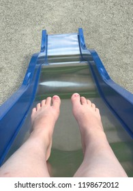 Girl going down slide in summer - view of feet