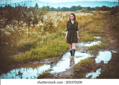 girl going on rural road in time a rain